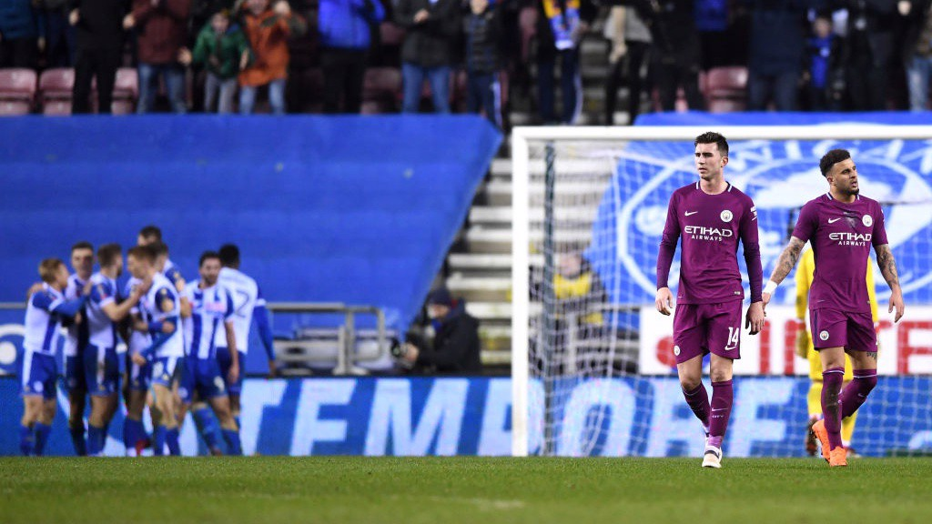 DEJECTION: Aymeric Laporte gets back into position as Wigan celebrate.