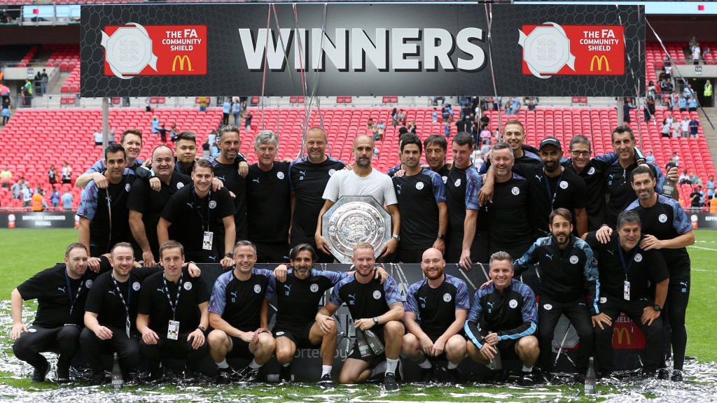 WINNING FORMULA: Pep Guardiola's staff pose with the latest trophy in their collection.
